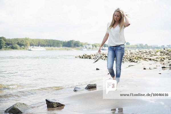 Deutschland  Düsseldorf  junge Frau am Rheinufer spazierend