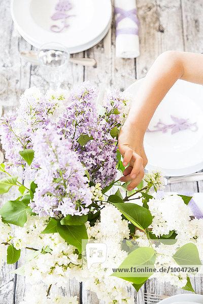 Mädchen beim Tischdecken  lila Blumen
