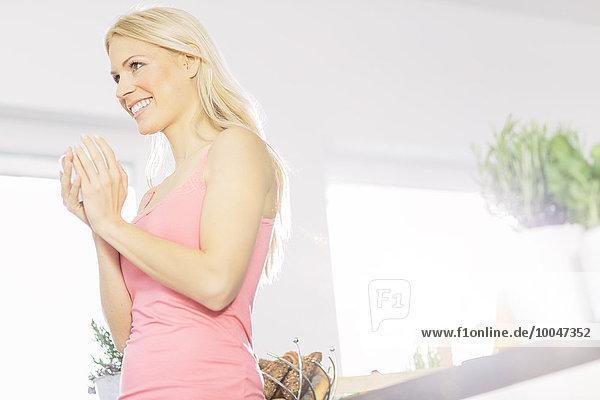 Lächelnde junge blonde Frau mit einer Tasse Kaffee in der Küche