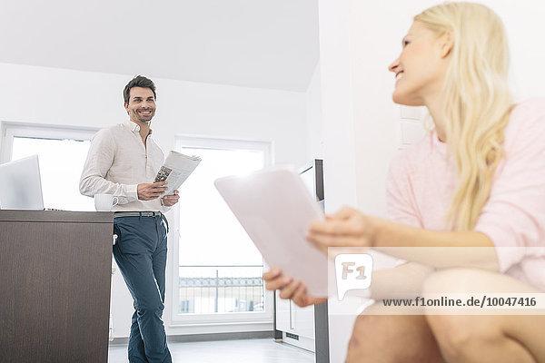 Paar mit digitalem Tablett und Zeitung zu Hause