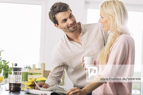 Paar mit Tasse Kaffee und Zeitung in der Küche