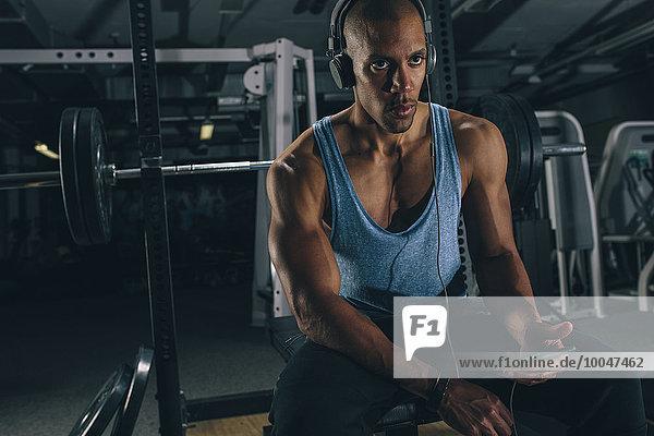 Portrait eines jungen Mannes bei einer Pause im Fitnessstudio