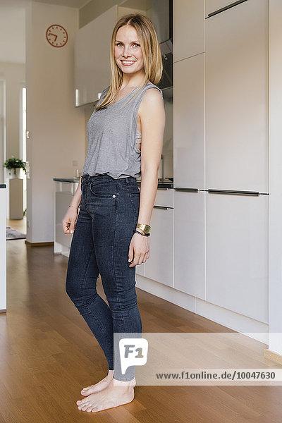 Lächelnde  blonde Frau steht barfuß in der Küche.