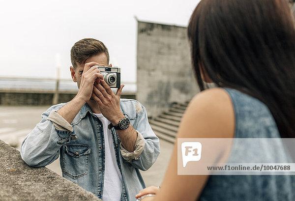 Spanien  Gijon  junger Mann beim Fotografieren seiner Freundin mit einer alten Kamera