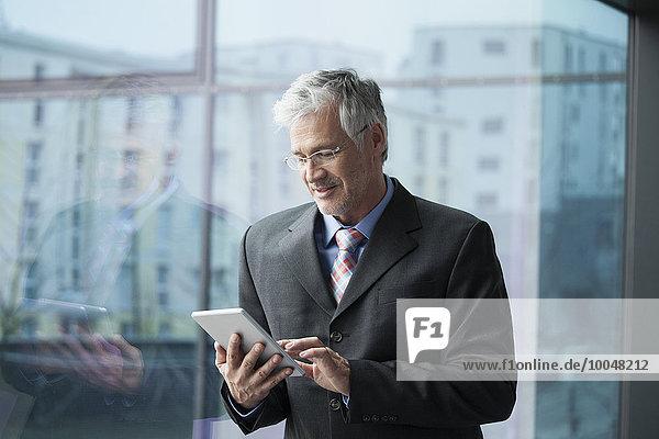 Geschäftsmann am Fenster stehend mit digitalem Tablett