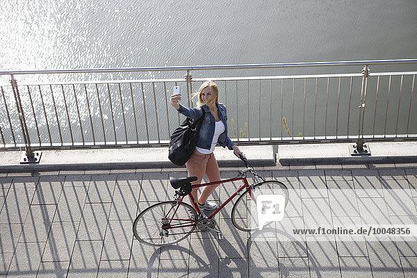 Deutschland  Düsseldorf  blonde Frau mit Fahrrad vor dem Rhein stehend mit einem Selfie mit Smartphone