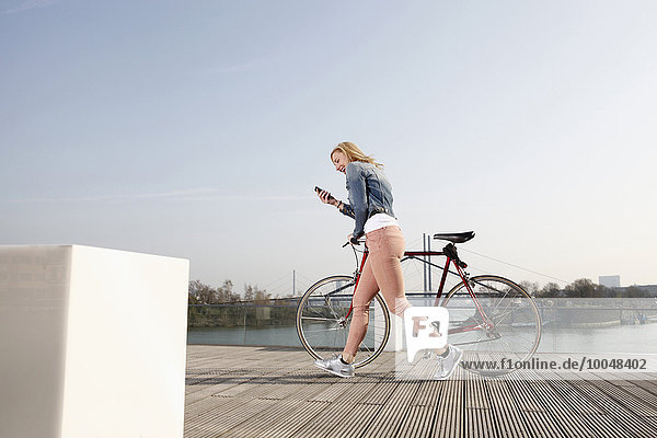 Germany  Duesseldorf  happy blond woman with bicycle and smartphone walking in front of Rhine River