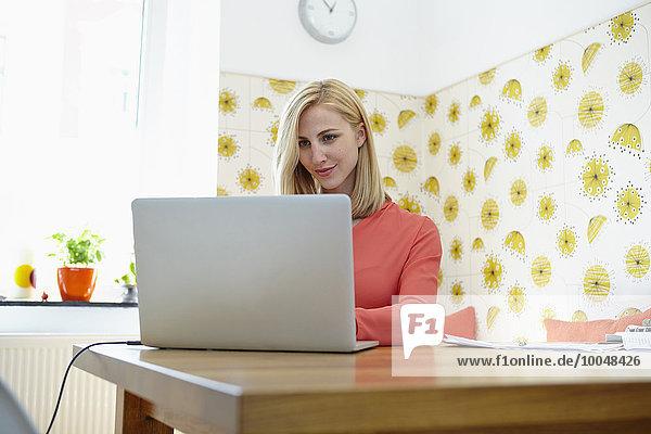 Junge Frau mit Laptop im Home-Office