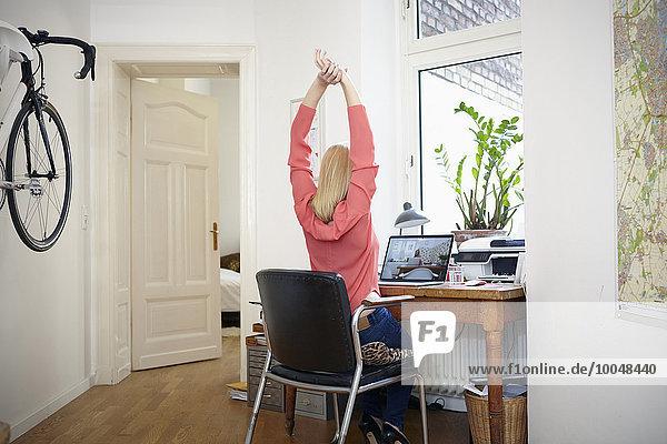 Frau sitzt am Schreibtisch in ihrem Arbeitszimmer und streckt sich.
