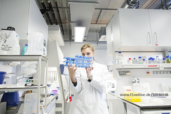 Young female scientist working at biological laboratory inspecting samples