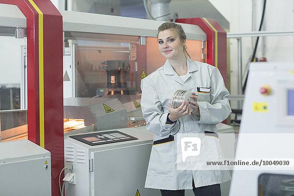 Junge Frau in der Fabrik mit Rollen