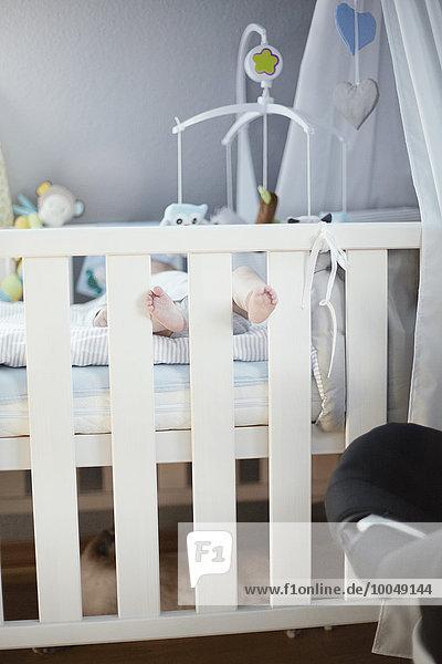 Baby in der Wiege liegend mit herausstehenden Füßen Baby in der Wiege liegend mit herausstehenden Füßen