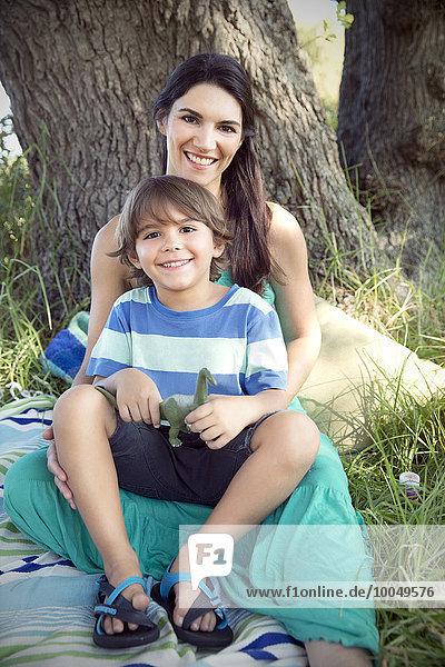 Porträt der glücklichen Mutter mit Sohn am Baum