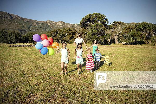 Glückliche Familie läuft mit Luftballons auf der Wiese