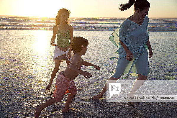 Familienspiel am Strand bei Sonnenuntergang