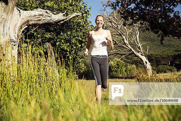 Lächelnde Frau beim Joggen in ländlicher Landschaft