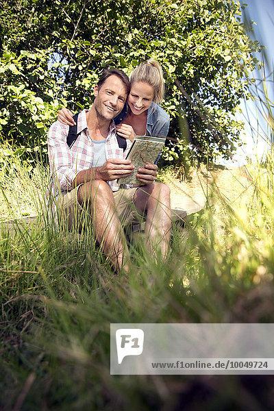 Fröhliches Wanderpaar mit Landkarte in der Pause