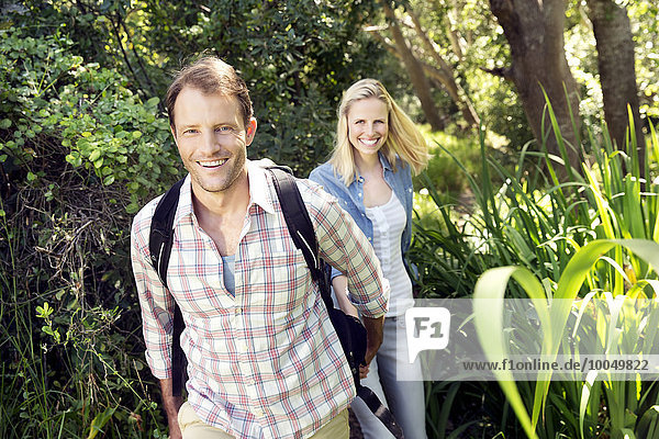 Smiling couple hiking hand in hand in forest