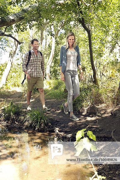 Lächelndes Paar beim Wandern auf dem Waldweg