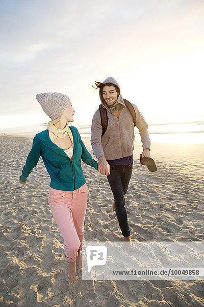 Junges Paar bei Sonnenaufgang am Strand spazieren gehen