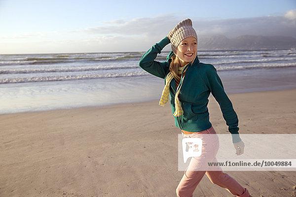 Lächelnde junge Frau beim Spaziergang am Strand