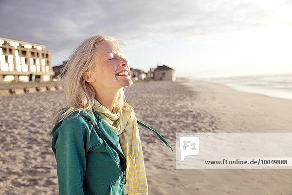 Lächelnde junge Frau am Strand bei Sonnenaufgang mit geschlossenen Augen
