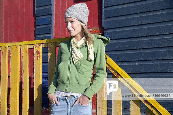 Junge Frau vor bunter Strandhütte