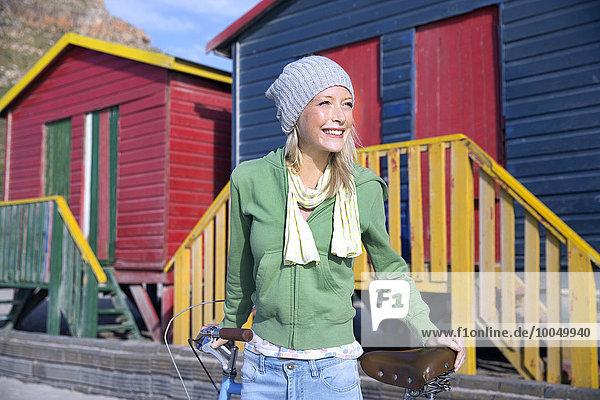 Lächelnde junge Frau mit Fahrrad vor bunten Strandhütten
