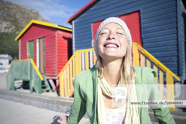 Glückliche junge Frau vor bunten Strandhütten