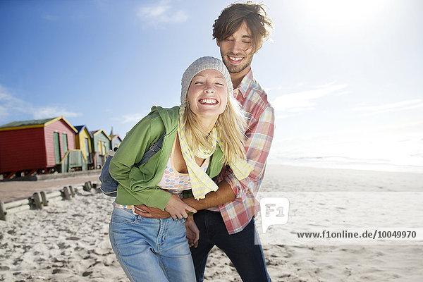 Verspieltes junges Paar am Strand