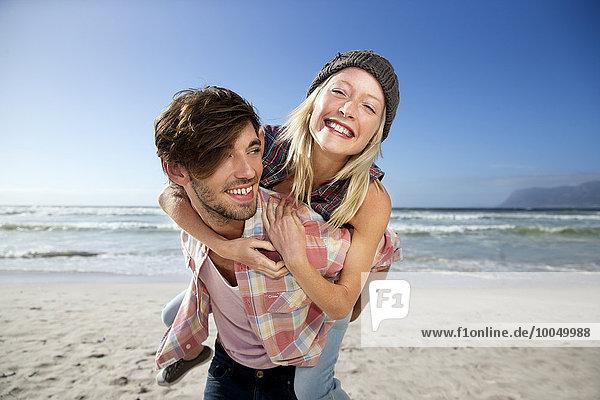 Junger Mann mit Freundin Huckepack am Strand