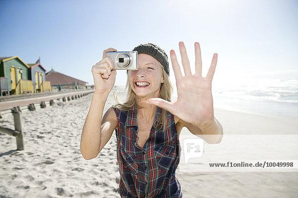 Junge Frau beim Fotografieren am Strand