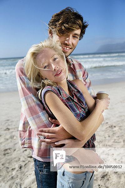 Glückliches junges Paar,  das sich am Strand umarmt.