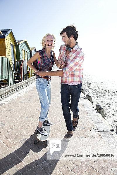 Junger Mann hilft Freundin auf Skateboard an der Strandpromenade