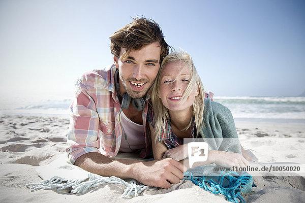 Glückliches junges Paar am Strand liegend
