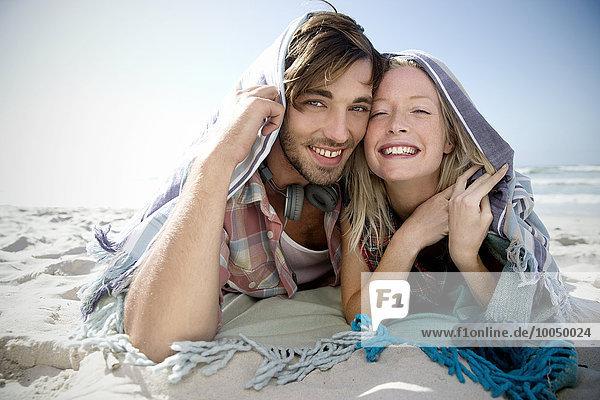 Ein glückliches junges Paar liegt am Strand unter einer Decke.