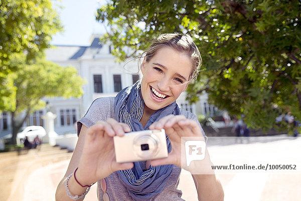 Porträt einer glücklichen jungen Frau mit Kamera