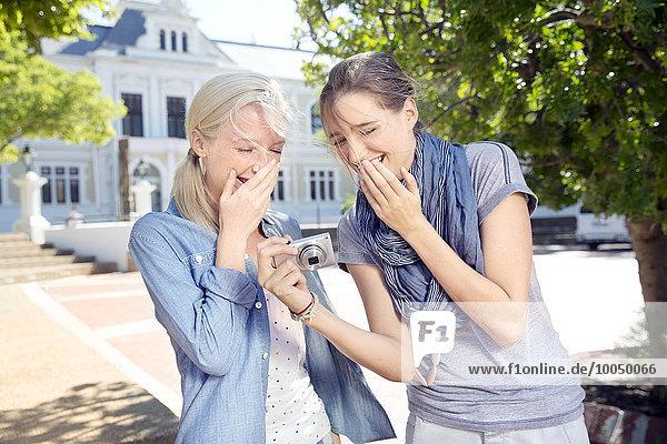 Zwei lachende junge Frauen im Freien mit Blick auf die Kamera