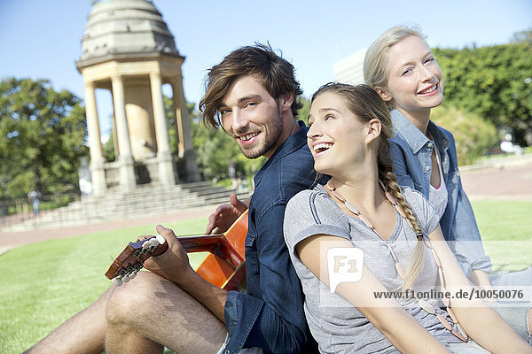 Glückliche Freunde mit Gitarre im Park