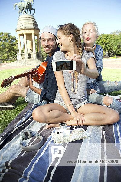 Glückliche Freunde im Park mit einem Selfie