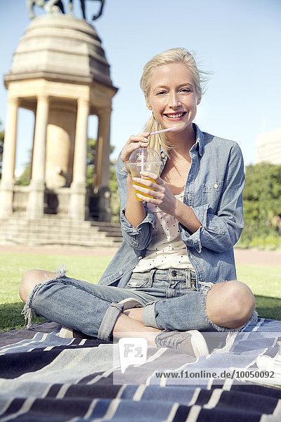 Junge Frau im Park mit Erfrischungsgetränk