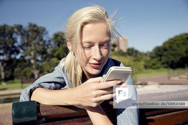 Junge Frau auf Parkbank mit Blick aufs Handy