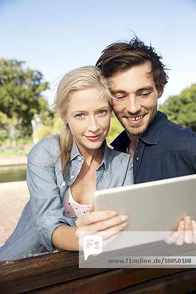 Junges Paar mit digitalem Tablett auf Parkbank