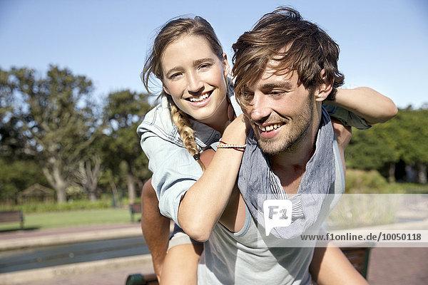 Glücklicher junger Mann mit Freundin Huckepack