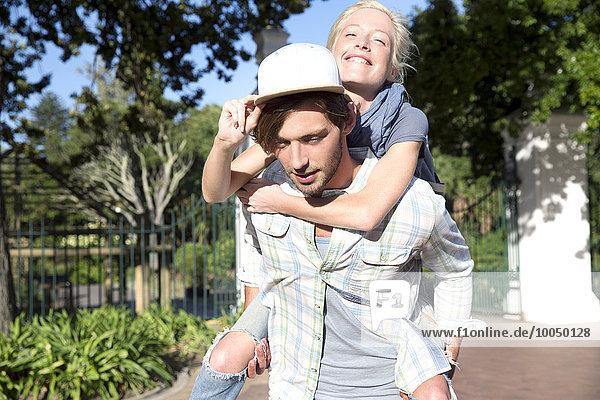 Junger Mann mit Freundin Huckepack