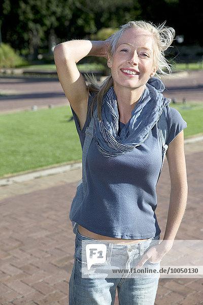 Porträt einer jungen Frau im Park stehend