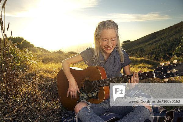 Fröhliche junge Frau spielt Gitarre auf Decke auf der Wiese