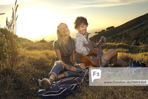 Glückliches junges Paar mit Gitarre auf Decke in der Wiese