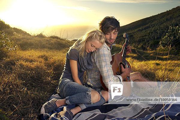 Junges Paar mit Gitarre auf Decke in der Wiese