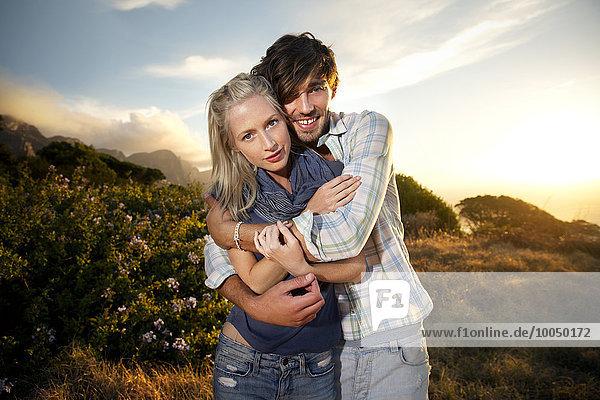 Zartes junges Paar an der Küste bei Sonnenuntergang